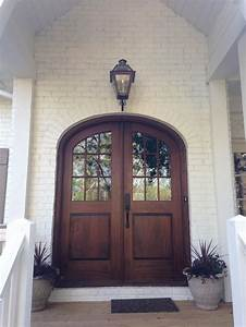 Brown Arched Glass Front Door On White Brick Home