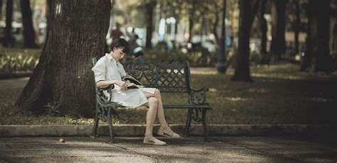 woman sitting  metal bench  park  reading book