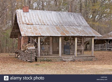 Log house with a tin roof and firewood stacker outside