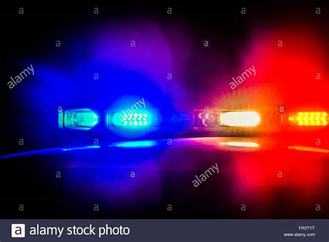 Red And Blue Flashing Police Car Lights Atop A Patrol Car