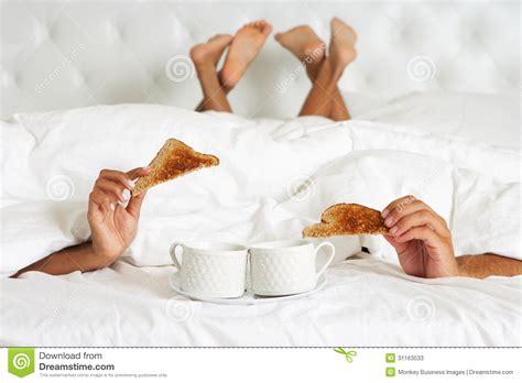 In Bed by Hiding Duvet Enjoying Breakfast In Bed Stock