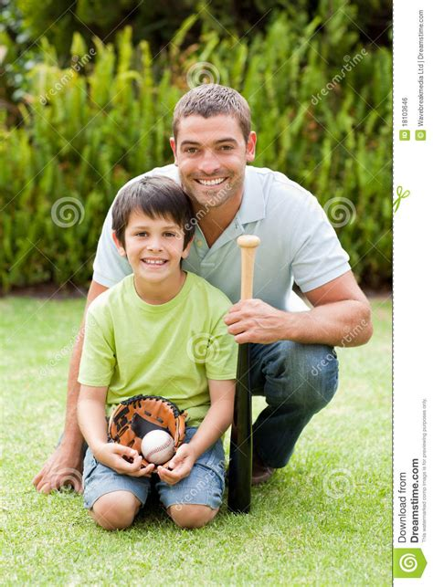 happy father   son playing baseball stock photo