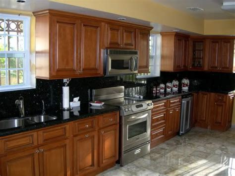 oak and black kitchen cabinets golden oak kitchen cabinets with black countertops