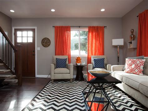 taupe living room  orange curtains  chevron rug hgtv