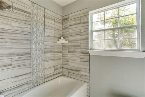 full bathroom with tiled wall showerbath drop in bathtub