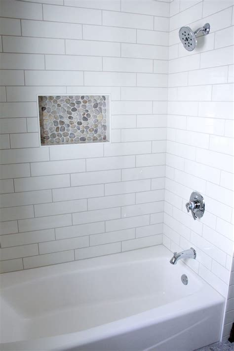 White Tiled Shower with Accent Neutral Pebble Tile Niche