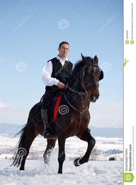 young man riding horse outdoor  winter stock photo
