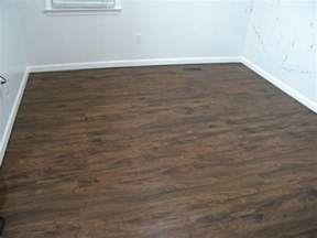 brown wooden vinyl plank flooring matched with white wall plus white baseboard molding