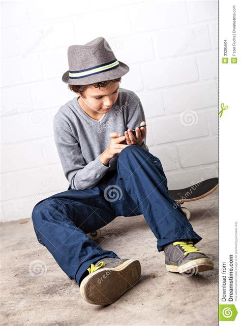 cool boy sitting   skateboard holding  smartphone