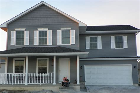 front view of my dark gray house with white shutters will do black door in spring for the