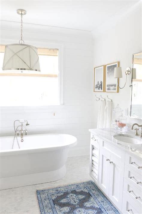 white bathroom with blue bath mat transitional