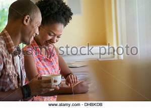 Two people seated at a coffee shop table by a window ...