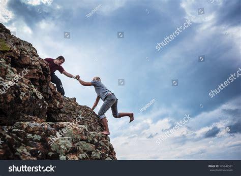 Man Giving Helping Hand Friend Climb Stock Photo