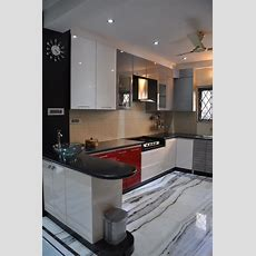 U Shaped Kitchen With Modern Cabinets And Wall Decor By