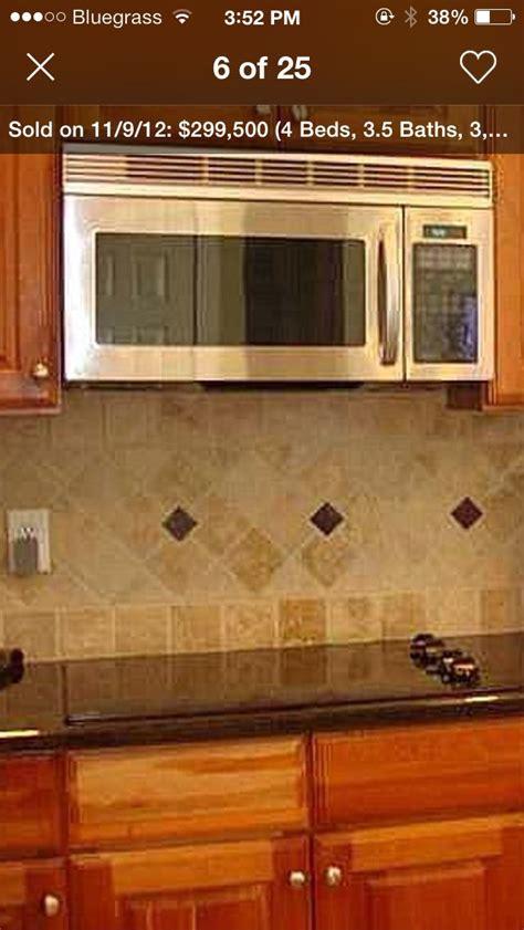 wood kitchen backsplash travertine tile with uba tuba granite and oak cabinets 1136