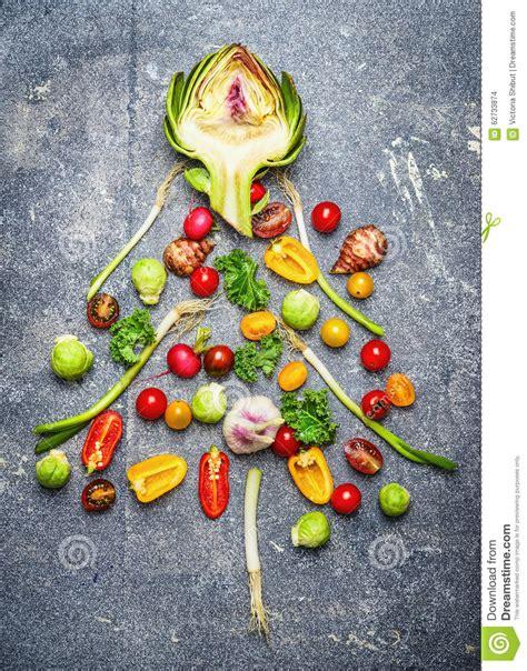 christmas tree made of fresh vegetables on gray rustic bac