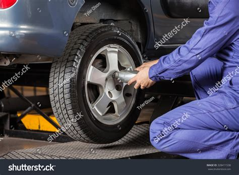 Midsection Of Male Mechanic Screwing Car Tire With