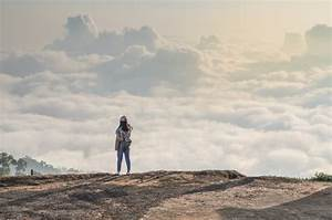 Woman standing alone on cliff over clouds landscape and ...