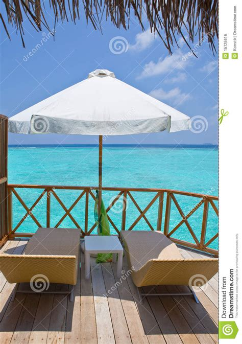 protection chaise chaise lounges and sun protection umbrellas on a wooden