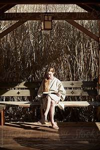 woman reading book on bench in nature wearing linen robe With robe bench