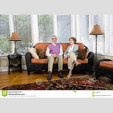 Happy Senior Couple Sitting On Living Room Couch Stock