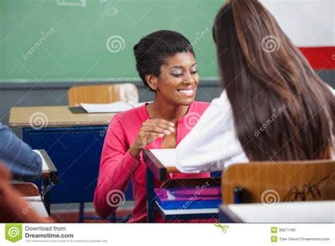 female teacher teaching teenage schoolgirl  desk stock