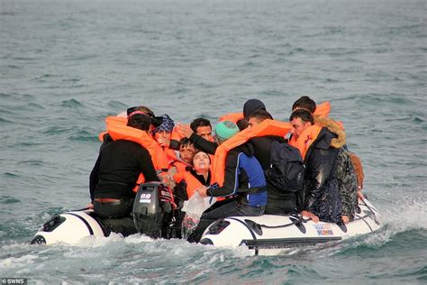 Migrants packed into tiny dinghy desperately bail out ...