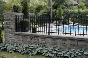Wrought Iron Bench With Cushion by Field Stone Wall With Ornamental Iron Fence Modern