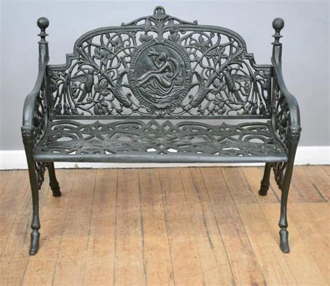 a decorative black painted cast iron garden bench