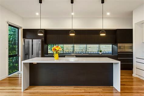 Modern kitchen with stone island bench, feature lighting