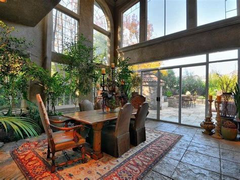 Dining Room In Atrium-style Home With Two Story Windows, Indoor Gardens And Large Wooden Table