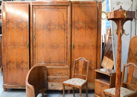 robe de chambre gar輟n een slaapkamer wortelfineer bestaande uit een driedeursgarderobe een kaptafel met spiegel een kapstok twee stoelen een voetbankje twee
