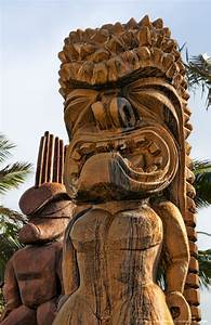 Hawaii, Oahu, Large wooden tiki statues greet visitors ...