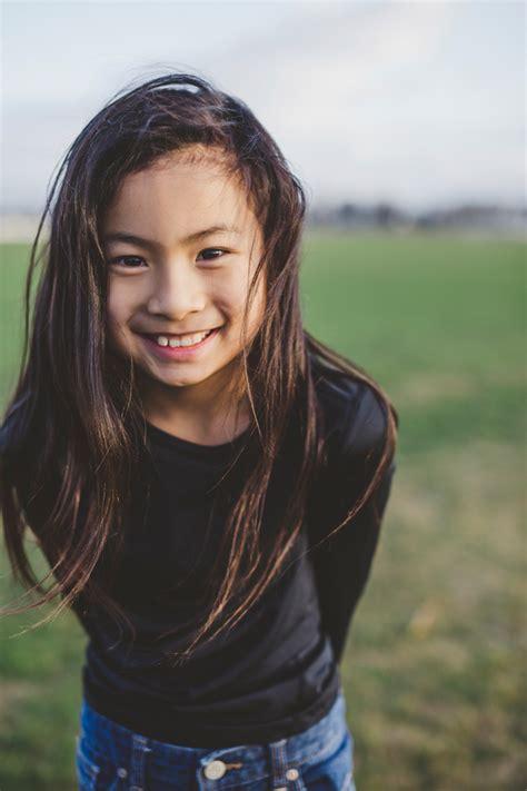 Cute elementary school aged asian girl happy in windy field