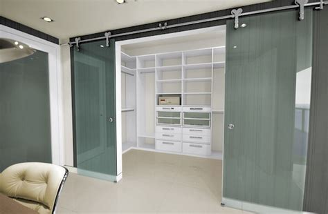 hanging glass doors and a white walk in closet with glass