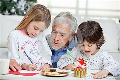 grandfather assisting children  writing letters stock