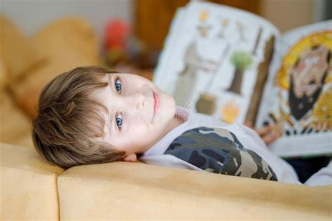 cute boy reading  book   couch stock image image