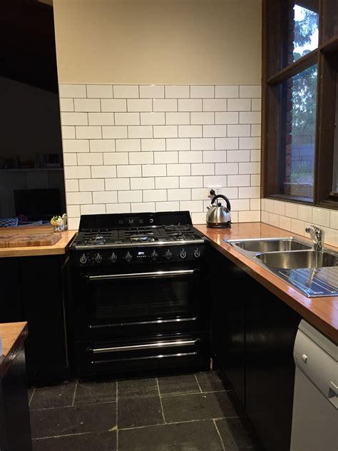 black smeg stove white subway tiles grey grout vic ash