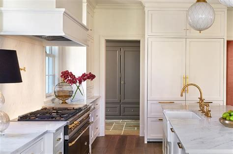 cream kitchen cabinets  brass pulls  black french stove transitional kitchen