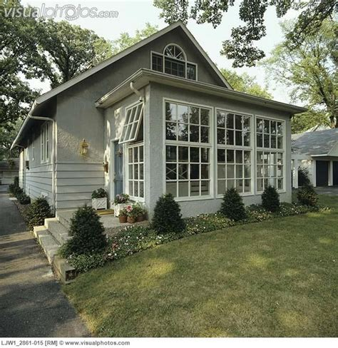 sunrooms front  small grey stucco bungalow addition  sunroom border garden  house