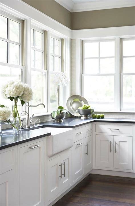 White Farmhouse Sink With White Custom Cabinets And Black