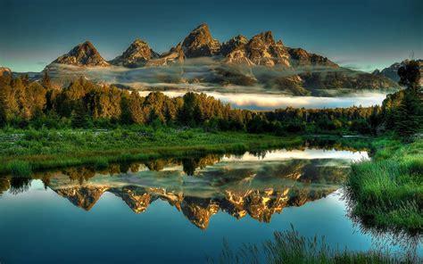 landscape rocky mountain peaks pine forest mist