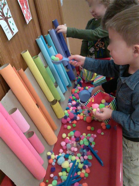 pom pom sorting using tongs and scoops sensory table 690 | cb073948dbb6745b88df4f01b0b76b8b