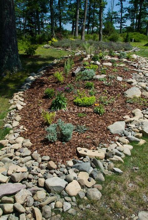garden bed mulched  hillside slope bordered  native rocks  stones  sunny summer spot