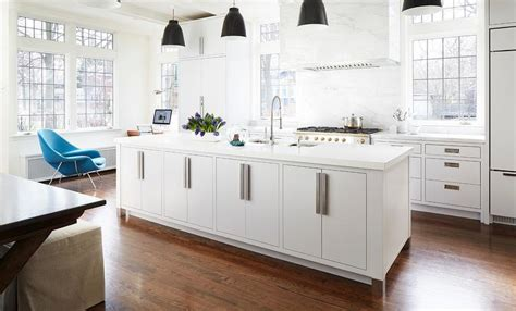white kitchen with black island white center island with black industrial pendant lights