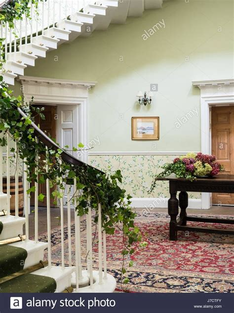 Sweeping staircase in large entrance hall with antique rug