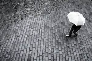 Woman with umbrella in rain on a cobbled street, black and ...