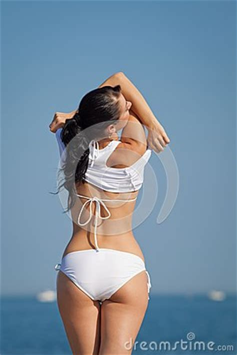 attractive brunette  white swimwear undressing