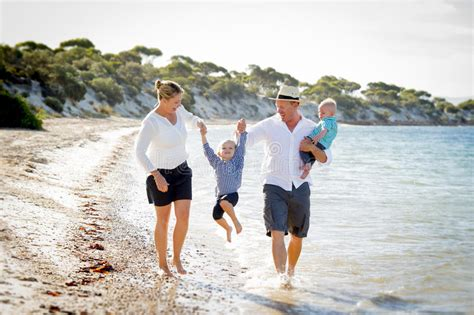 Young Happy Beautiful Family Walking Together On The Beach Enjoying Summer Holidays Stock Photo