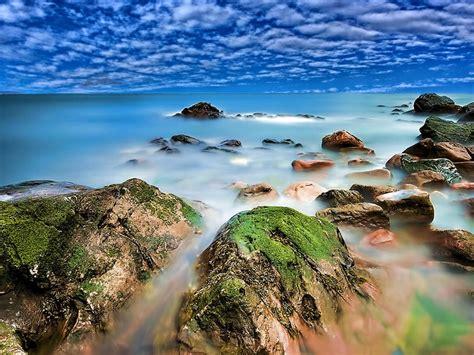seaside coastline red rocks  green moss turquoise